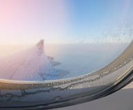 Close up frame of plane window seeing ice crystals in foreground and aircraft`s wing and horizon in background Royalty Free Stock Image