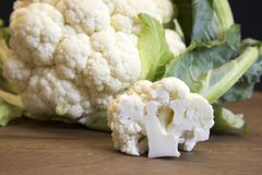 Raw cauliflower head and floret on wooden board. Close up of freah raw cauliflower head and floret on wooden board Stock Image