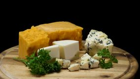 Close up for french delicious aged cheeses choped and served on wooden board isolated on black background. Frame royalty free stock image