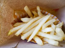 Close up french fries stick in paper bag. royalty free stock photos