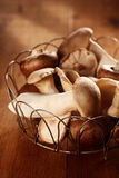 Close up of fresh autumn King Oyster mushrooms. Pleurotus eryngii, displayed in a rustic wire basket ready for use in the kitchen in savory dishes and salads stock photos