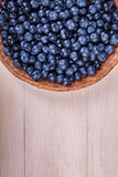 Close-up of fresh and bright blueberries. Healthy, ripe, raw and bright dark blue berries on a wooden background. Copy space. Stock Photography