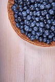 Close-up of fresh and bright blueberry.  Healthy, ripe, raw and bright dark blue berries on a wooden background. Copy space. Royalty Free Stock Image
