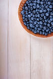 Close-up of fresh and bright blueberry. Healthy, ripe, raw and bright dark blue berries on a wooden background. Copy space. Royalty Free Stock Photography