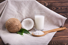 Close-up of fresh bright brown coconuts, organic coco milk, and a wooden spoon with coconut chips on a dark wooden. A large glass of tasty coco milk and a wooden Royalty Free Stock Image