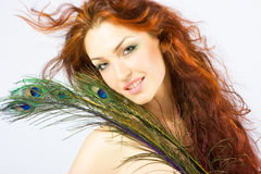 Close-up fresh bright lady with long red hair. Close-up beautiful luxury fresh bright young lady smiling in studio shot with beautiful make-up with peacock Stock Photos