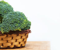 Close up on Fresh broccoli solated in basket on wood and white background Royalty Free Stock Photo