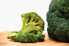 Close up on Fresh broccoli solated on wooden and white background Royalty Free Stock Photo