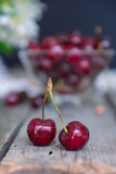 Close up Fresh cherries with glass vase with berries on the old wooden table. Soft selective focus. Summer rustic concept Stock Photos