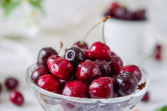 Close up Fresh cherry fruit in glass vase, other dishes with berries and jar with jasmine and wildflowers on the light marble tabl. E. Soft selective focus stock images
