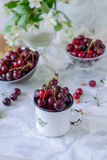 Close up Fresh cherry fruit in white mug, other dishes with berries and vase with jasmine flowers on the light marble table. Soft. Selective focus. Summer stock image