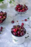 Close up Fresh cherry fruit in white mug, other dishes with berries and vase with jasmine flowers on the light marble table. Soft. Selective focus. Summer royalty free stock photos