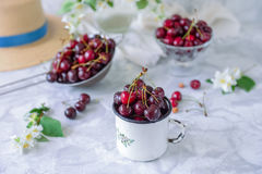 Close up Fresh cherry fruit in white mug, other dishes with berries and vase with jasmine flowers on the light marble table. Soft. Selective focus. Summer stock photography