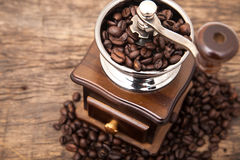 Close up fresh coffee bean in coffee bean grinder. Next to coffee bean on wooden table top Royalty Free Stock Photos