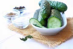 Cucumbers in a ceramic bowl on  sackcloth and spices for picklingfermenting- dill seeds, pepper, salt on a white wooden table. stock images
