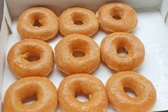 Fresh donuts in white paper box stock images