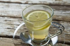 Close up of fresh ginger tea with lemon slice on weathered table. Close up of fresh ginger tea with lemon slice on weathered wooden table Stock Image