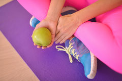 Close-up of fresh green apple held by a woman sitting at fitness class Royalty Free Stock Photography