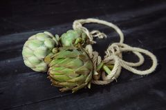 Close up Fresh green artichokes with braided rope on the black wooden kitchen table lightened by morning window light. Farmer. Harvest, local market. Selective royalty free stock images