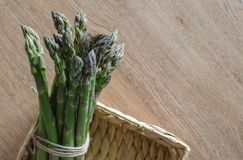 Close-up of fresh green asparagus wrapped with rope in the rusti. C basket. top view Stock Images
