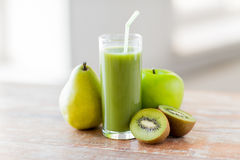 Close up of fresh green juice and fruits on table. Healthy eating, organic food and diet concept - close up of fresh green juice glass and fruits on table stock photos