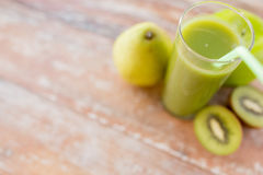 Close up of fresh green juice and fruits on table Royalty Free Stock Images