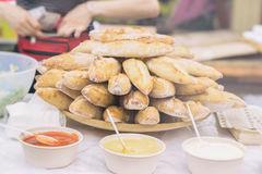 Close-up of fresh hot baguettes and diffrent sauces for sandwiches, selective focus. Hands of seller in the background Royalty Free Stock Photography