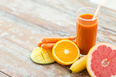 Close up of fresh juice glass and fruits on table Stock Images