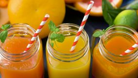 Close up of fresh juices in mason jar glasses. Healthy eating, drinks, diet and detox concept - close up of fresh fruit or vegetable juices in mason jar glasses stock footage