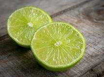 Lime cut in half on wood surface stock images