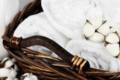 Close Up of Fresh Laundered Towels Soap and Cotton Flowers. Laundry basket filled white fluffy towels, cotton flowers and a bottle of liquid soap against a royalty free stock photos