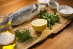 Close up of a fresh lemon lying on a wooden plate with herbs, olive oil, spices and fish Stock Images