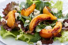 Close-up of fresh mixed salad. Lettuce and arugula leaves with grilled peach and blue cheese. Healthy food royalty free stock image