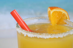 Close up fresh orange juice in glass on the beach Stock Images