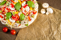 Close-up of fresh pizza lying on the baking paper Stock Image