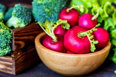 Fresh seasonal vegetables on wooden surface. Close-up fresh radish in wooden bowl and broccoli in wooden box. Healthy diet concept, selective focus Stock Image