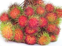 Close up fresh rambutans are collected from both branches and ti. Ed together on white background Royalty Free Stock Images