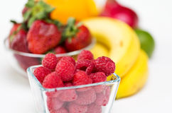 Close up of fresh raspberry and fruits on table. Healthy eating, food and diet concept - close up of fresh raspberry and fruits on table Royalty Free Stock Photos
