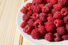 Close up of fresh raspberry on wooden boards. Close up of fresh raspberry on a white plate on wooden boards Stock Photo