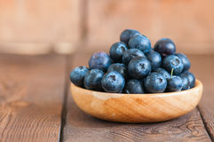 Close up of fresh raw blueberries served in a wooden plate. Wood. En background and copy space. Helthy eating and gardening concept Royalty Free Stock Photos