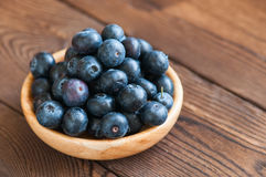 Close up of fresh raw blueberries served in a wooden plate. Wood. En background and copy space. Helthy eating and gardening concept Royalty Free Stock Photo