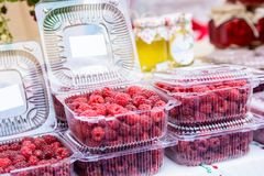 Raspberries in plastic box in supermarket. Close up fresh raw raspberries for sale in market Stock Photos
