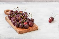 Close up of Fresh red cherries in glass bowl. Close up of Fresh red cherries on wooden plate on marble grey background . With copy space stock photos