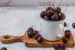 Close up of Fresh red cherries in glass bowl. Close up of Fresh red cherries on wooden plate in white enamel cup on marble grey background . With copy space royalty free stock images