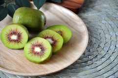 Close up Fresh Red Kiwifruit on Plate. Close up fresh pieces of red kiwifruit on wooden plate royalty free stock image