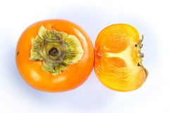 Close-up fresh ripe persimmons. Fresh ripe persimmons cut into half isolated on white background. Copy space Royalty Free Stock Photos