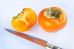 Close-up fresh ripe persimmons. Fresh ripe persimmons cut into half with sharp stainless steel metal knife isolated on white background. Copy space Royalty Free Stock Images