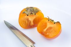Close-up fresh ripe persimmons. Fresh ripe persimmons cut into half with sharp stainless steel metal knife isolated on white background. Copy space Stock Photos