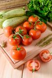 Close-up of fresh, ripe tomatoes with vegetables on wooden background. Top view Stock Images