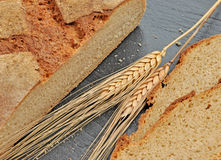 Close-up of fresh rustic bread with ears of wheat. stock photography